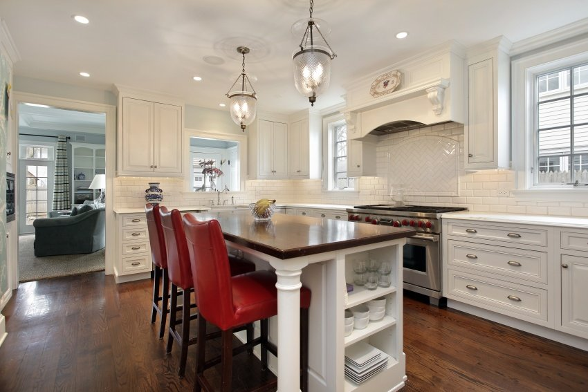 all-white kitchen with red chairs
