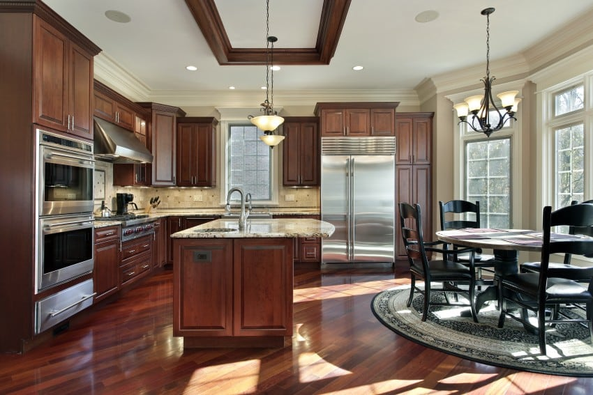dark wood cabinetry along with speckled granite countertops and tiled backsplashes