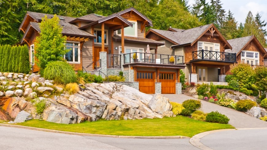 wood and stone house with 2 car garage doors