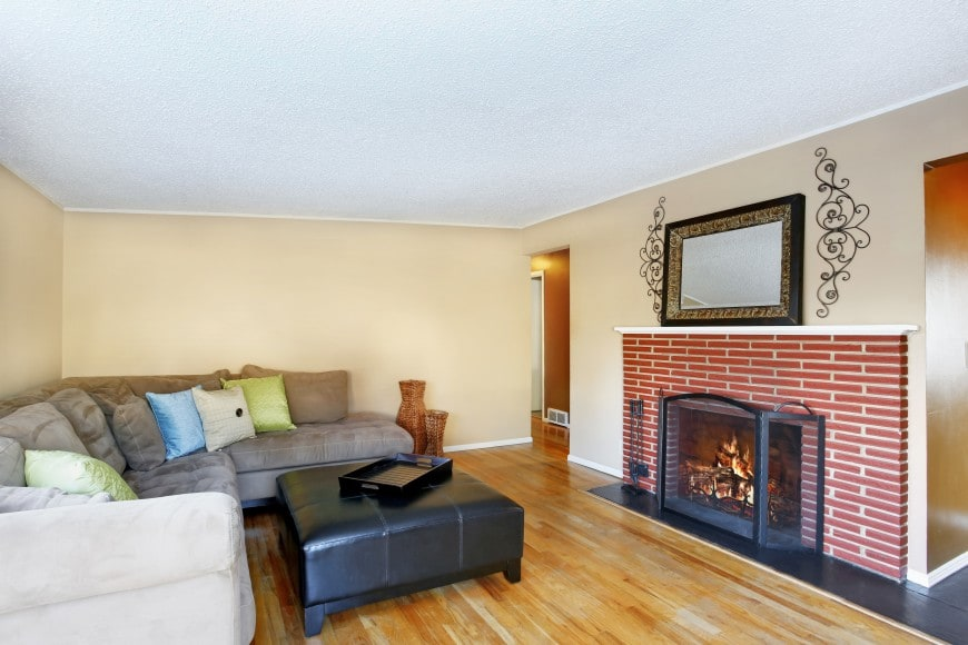 This simple living room design also features a red brick fireplace