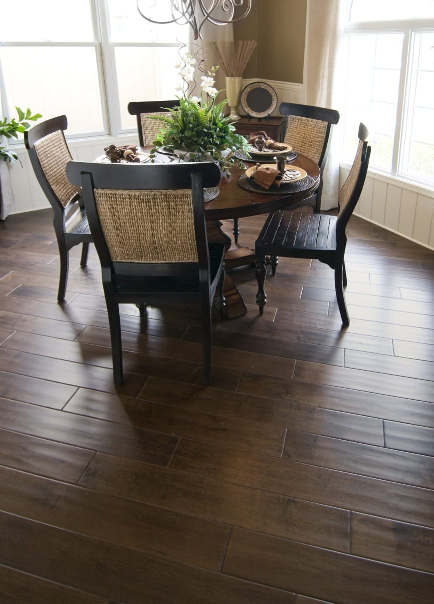 This dining room area features a dark hardwood floor, wainscot walls and large windows with light curtains