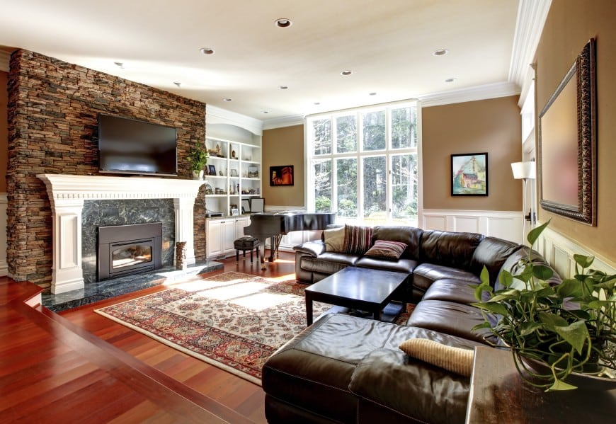 It has a hardwood floor, large windows and a drop ceiling with recessed lighting