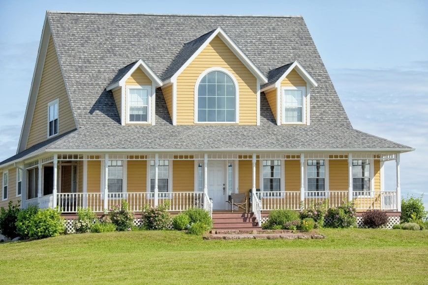 This farmhouse has a symmetrical front facade and a simple design in grey shingles and yellow siding