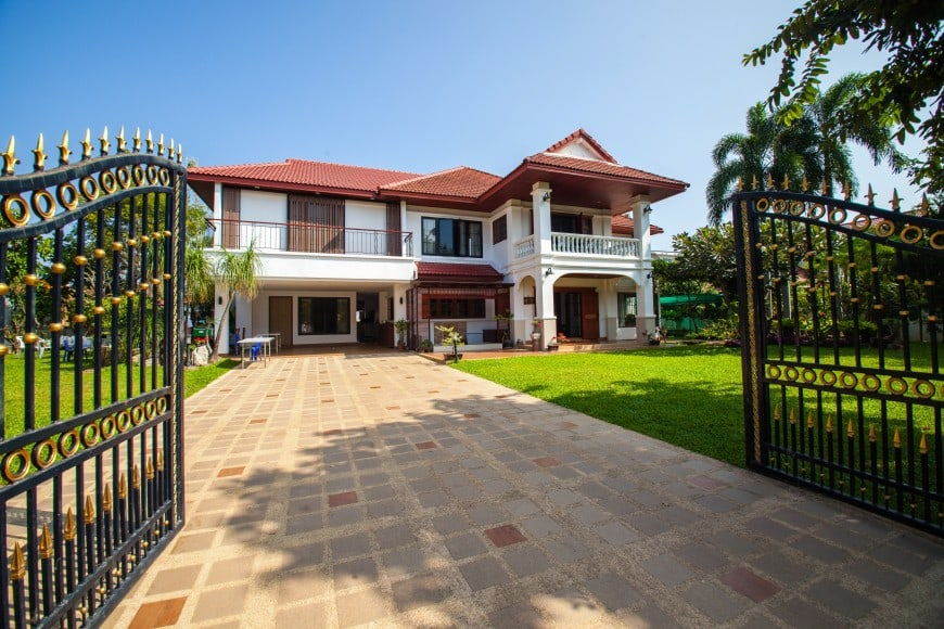 This luxurious house with a wrought iron fence and gate looks exquisite