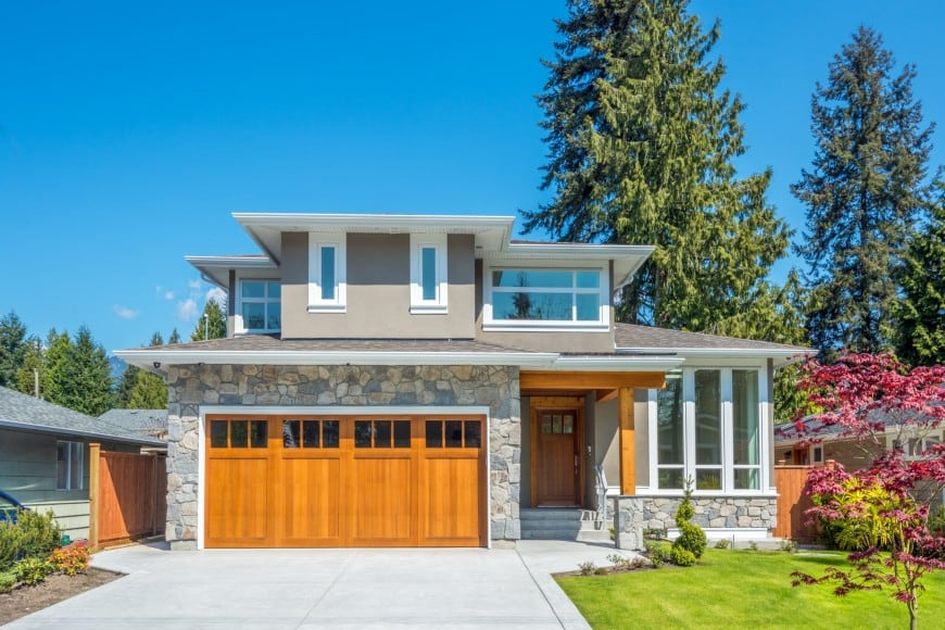 This house has a wide concrete-laid driveway that leads us to a large two-car garage