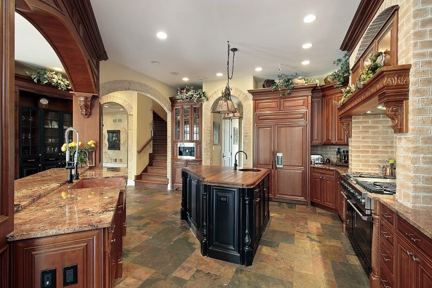 This custom kitchen design features dark wood cabinets with a triangular island counter in between.