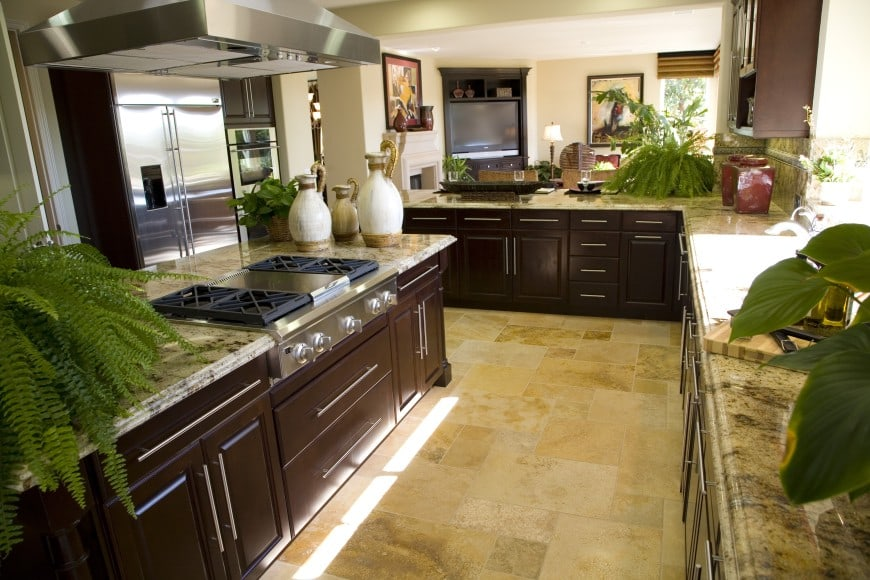this kitchen is set in dark wood and has granite countertops and backsplashes.