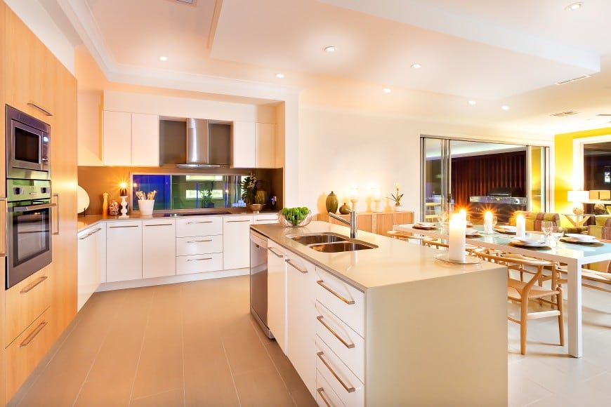 This L-shaped kitchen with an island counter and an open-concept floor plan is set in white and beech wood