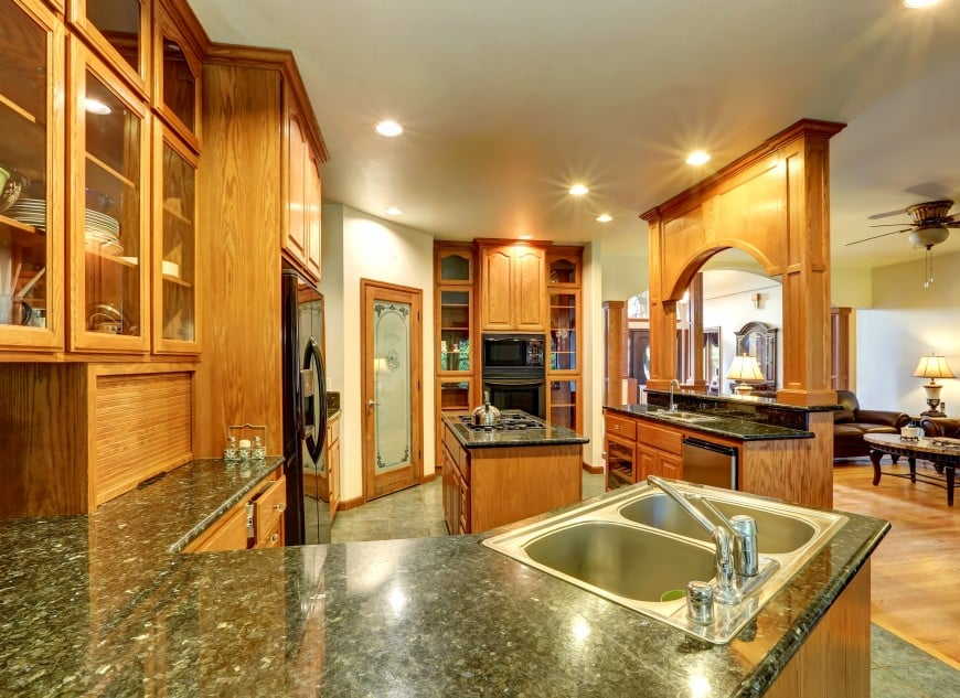 The kitchen is set in oak wood and dark granite, and features an island counter in the middle