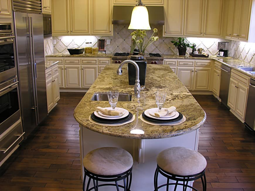This U-shaped design features a large island counter with a second sink and bar seating.