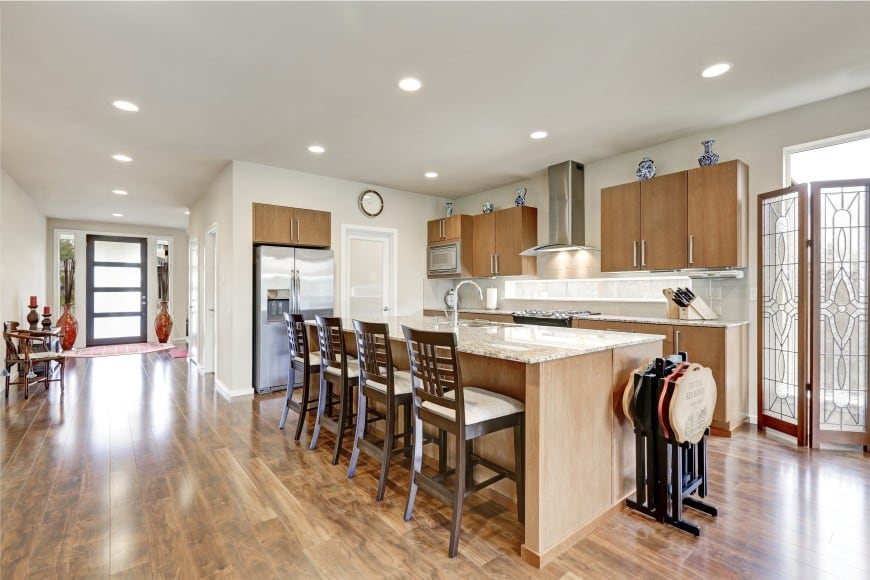 This modern kitchen design is set in light wood and features a large island counter that can easily accommodate four people