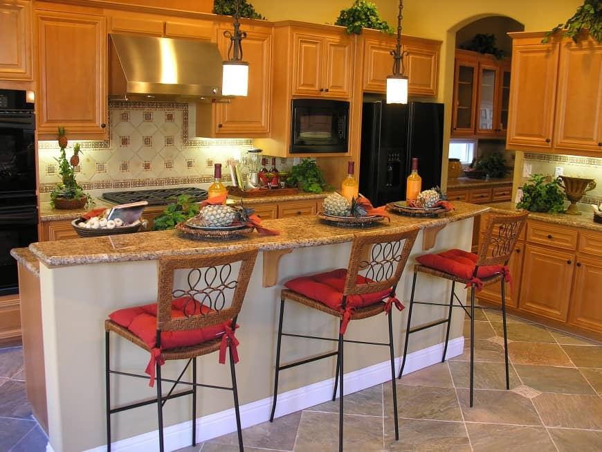 This cozy traditional kitchen features all-wood cabinets with granite countertops and tiled backsplashes