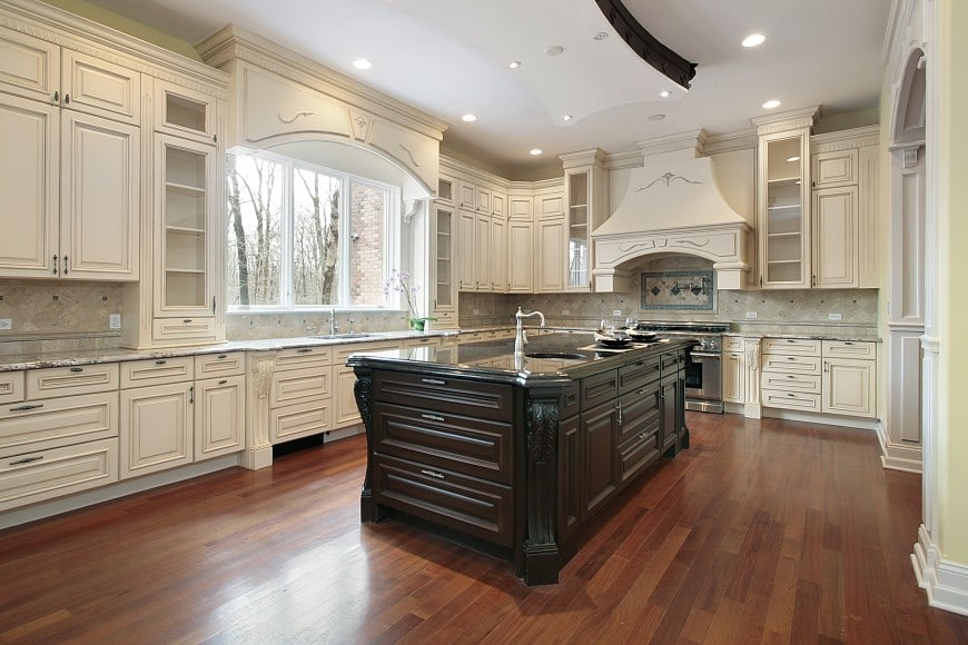 Feast your eyes on a fabulous kitchen design with eggshell-colored cabinets and a dark wood island counter.
