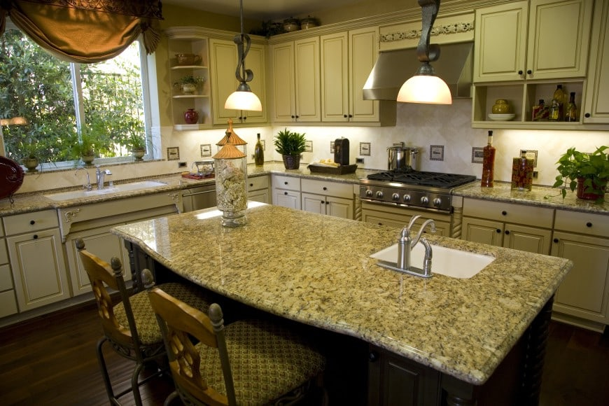 This traditional ivory-colored kitchen design features granite countertops and a dark wood island counter