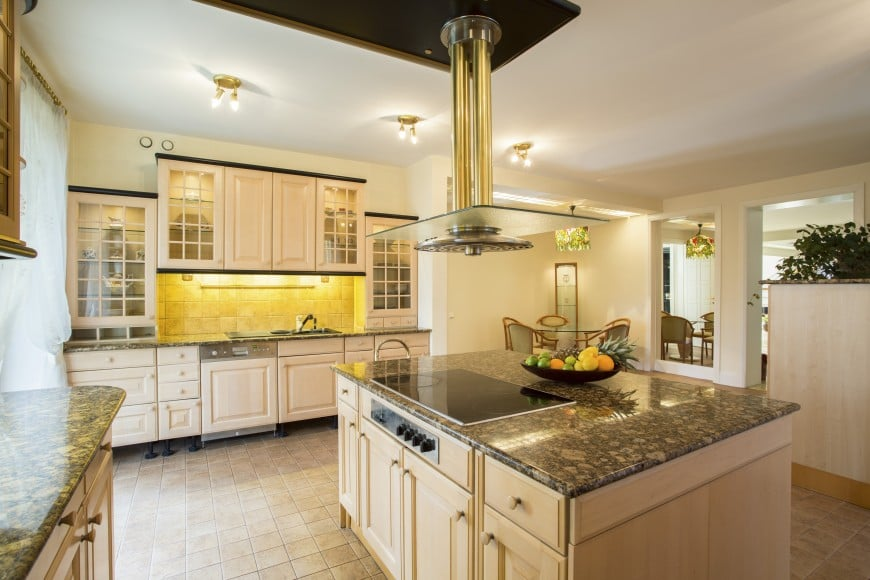 This transitional kitchen design is set in light-colored wood and speckled granite.