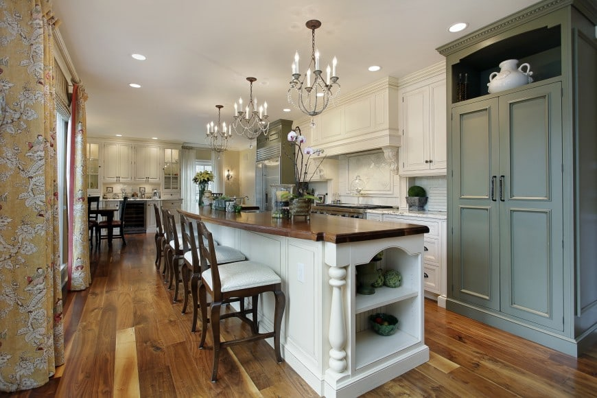 This kitchen design set in white and grey features an elongated island counter with a chocolate brown countertop