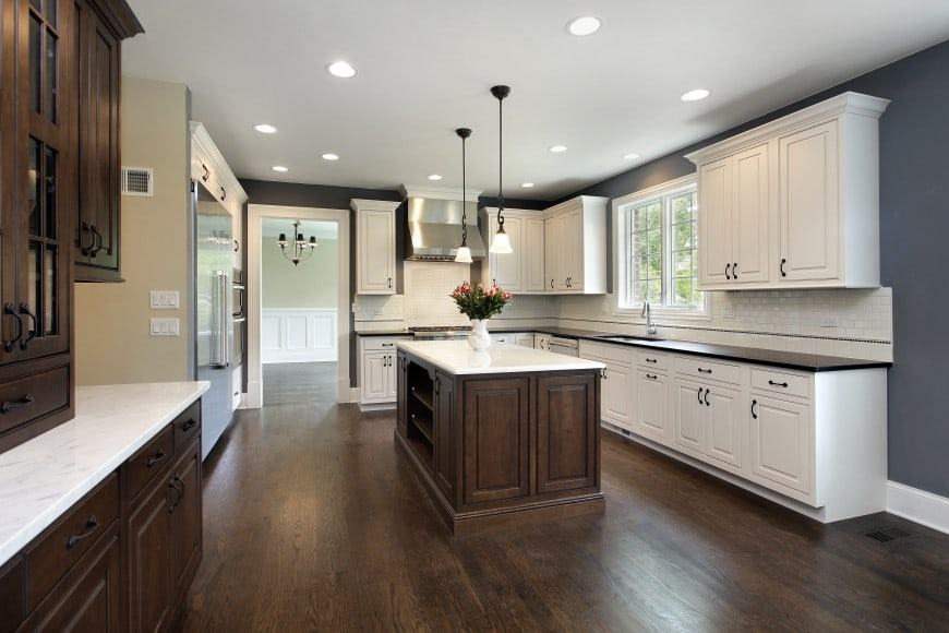 Here in this design we have dark-toned hardwood floors cabinets and island counter in the middle of the room.