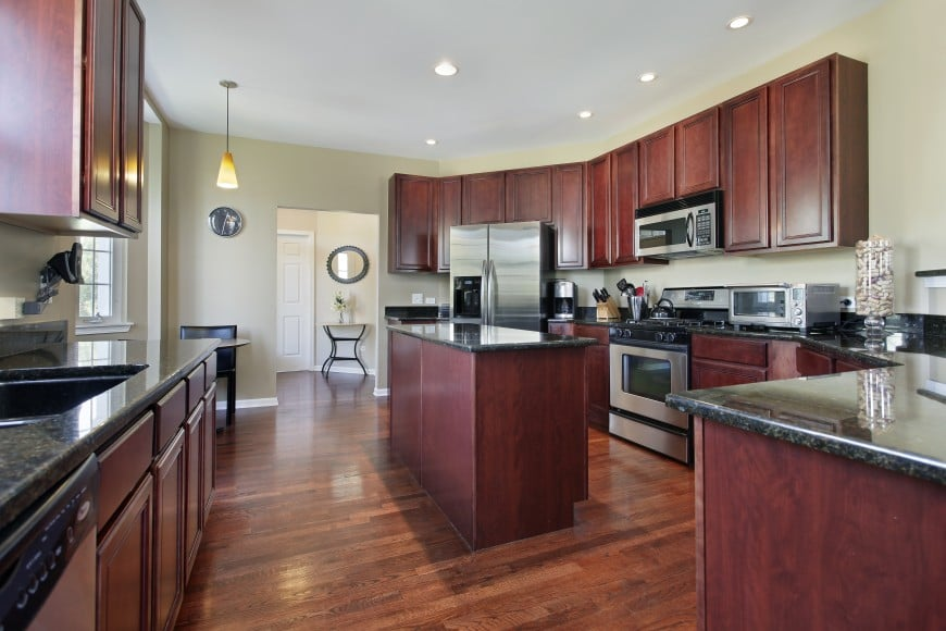 Here is an all-wood kitchen design with dark granite countertops and stainless steel appliances