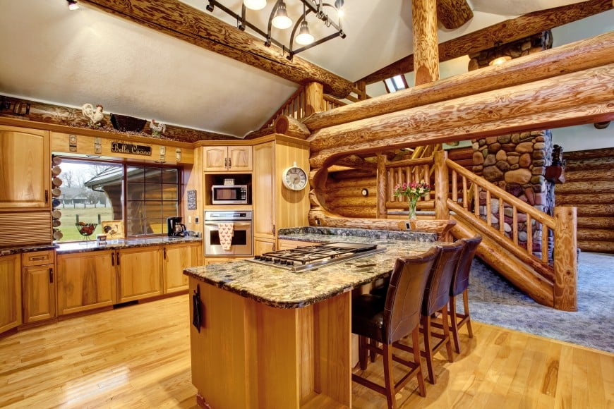 This log cabin kitchen design features all-wood cabinets with granite countertops and a kitchen bar counter