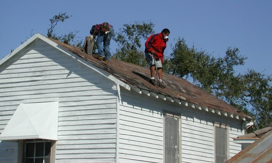 two roofers cleaning a roof