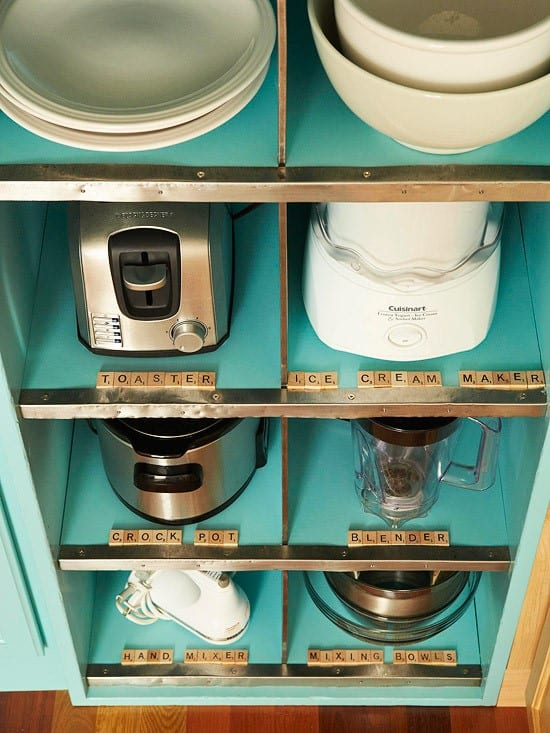 Appliances stored individually in the kitchen cabinet and labeled scrabble letters