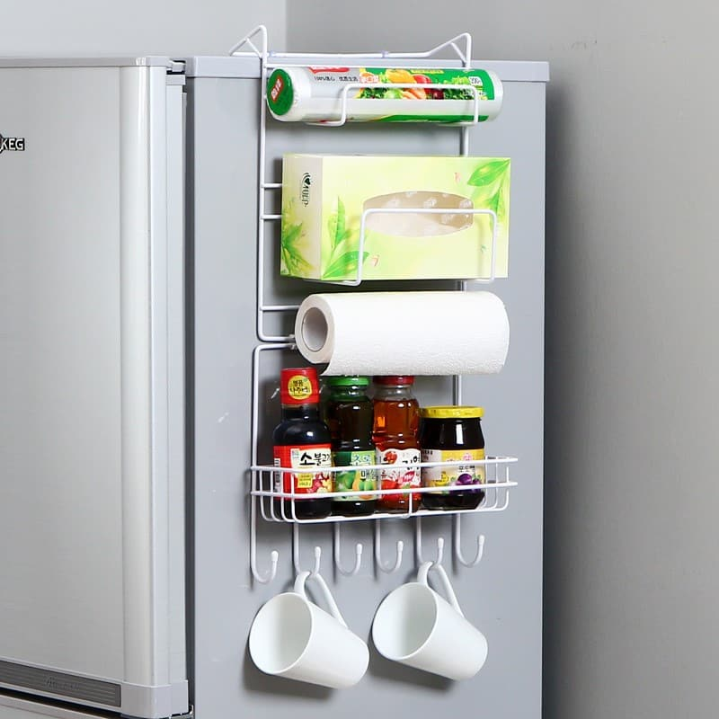 A rack filled with sauces and other kitchen items hanging from the side of the refrigerator
