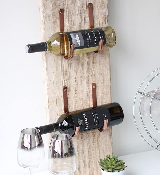 A wine rack made out of wood plank and having two bottle placed on it
