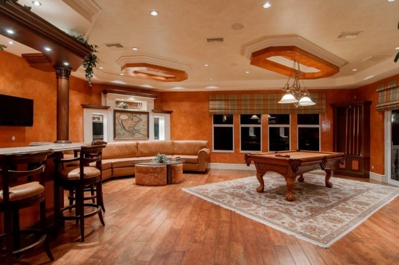 Room with a pool table, bar and sofa with hardwood flooring