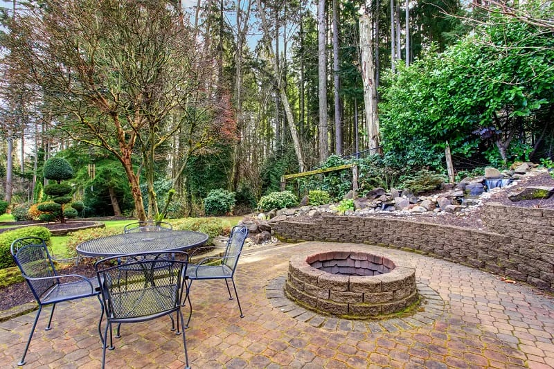 Vintage back patio with fire pit, furniture, and lots of greenery.