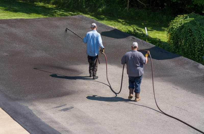 workers applying blacktop and asphalt sealer