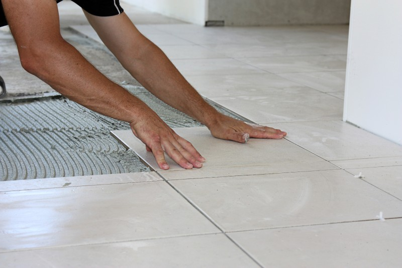 worker laying tile on floor
