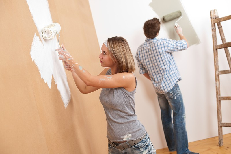 couple painting a wall in house